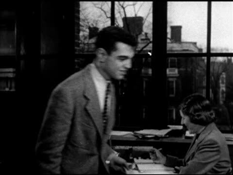 People walking down steps w/ columns BG MS Male student handing paper to woman at desk walking book aisle WS Shelf end signs American Literature...