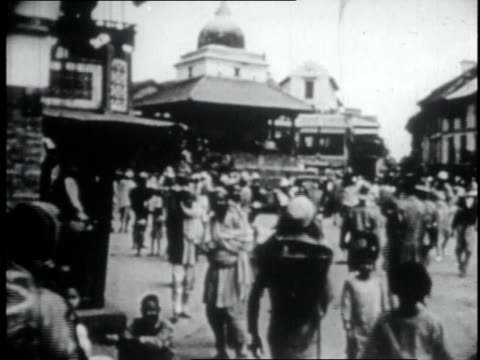 people walking down street / person standing at large pot with others sitting next to it - 1956 stock-videos und b-roll-filmmaterial