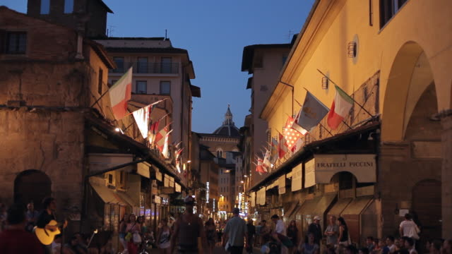 ws ld people walking down street with flags hanging from buildings / florence, italy - florence italy stock videos & royalty-free footage