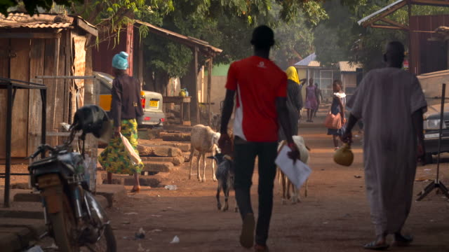 people walking down the street in ghana - povertà video stock e b–roll