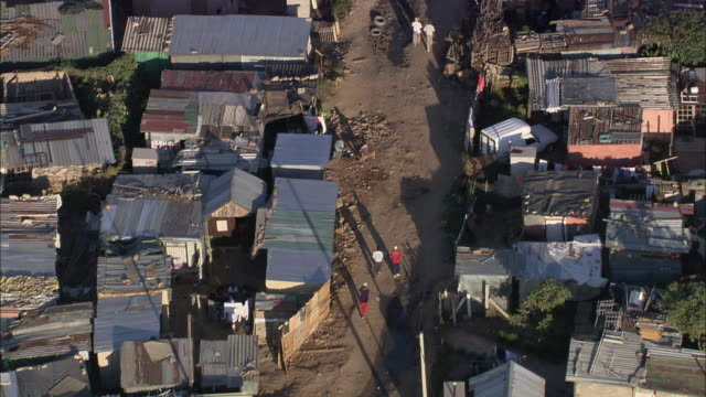 aerial ws ts people walking down track in township, johannesburg, gauteng, south africa - povertà video stock e b–roll