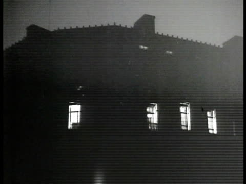 night people walking fg w/ clock at 900 pm bg ext building w/ upper floor lights on wilson wyatt working at desk w/ secretary looking over paperwork... - 1946 stock videos and b-roll footage