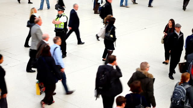 people walking in a london station watched by policeman - police force stock videos and b-roll footage