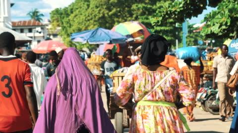 people walking in crowded market street of stone town, zanzibar, tanzania - africa stock videos & royalty-free footage