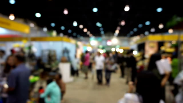 People walking in exhibition fair defocused background.