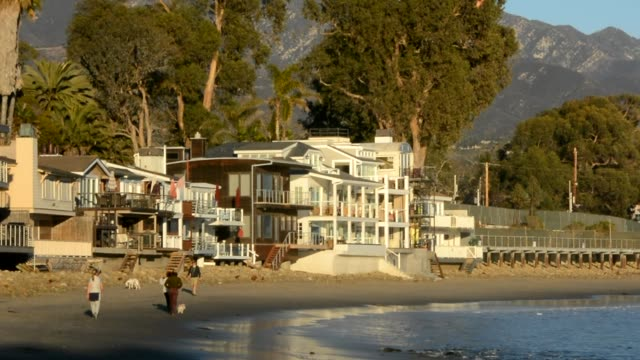 People walking in front of California beach house on the sand small ripply waves lapping the shore calm and restful day at the beach tranquil...
