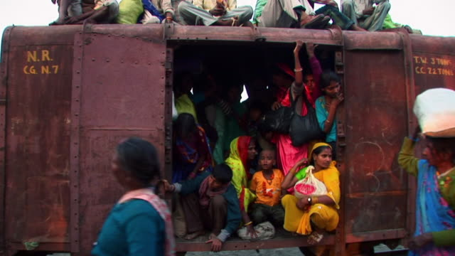 people walking in front of crowded train - dhoti video stock e b–roll