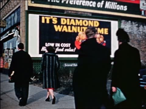 vidéos et rushes de 1941 people walking in front of diamond walnut billboard / chicago / industrial - prelinger archive