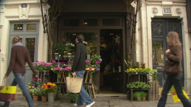 ms people walking in front of flower shop / paris, france - fioraio negozio video stock e b–roll