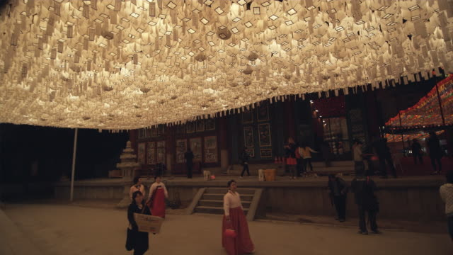 ws people walking in front of jogyesa temple under white paper lanterns, buddha's birthday, seoul, south korea - buddha's birthday stock videos and b-roll footage