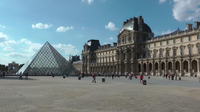 people walking in front of louvre museum - louvre stock videos and b-roll footage