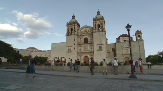ws people walking in front of santo domingo de guzman church / oaxaca, mexico - サントドミンゴ点の映像素材/bロール