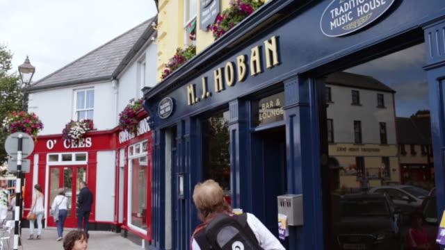 ms pan people walking in front of shops / westport, county galway, ireland - western script stock videos & royalty-free footage