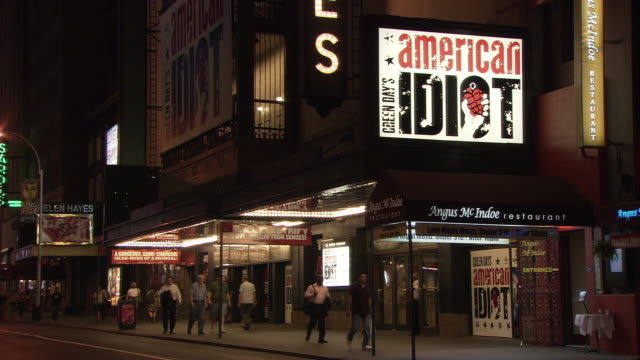ws people walking in front of st. james theatre with 'american idiot' musical ad illuminated at night, broadway / new york city, new york, usa - 前にいる点の映像素材/bロール