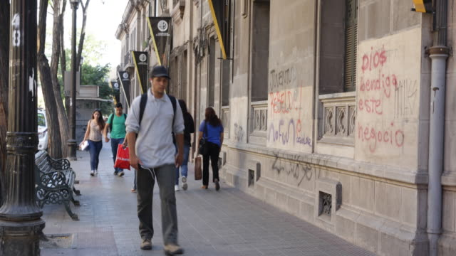 people walking in front of the university alberto hurtado in downtown santiago fixed on the walls are the universities flags with the weapons on them... - christian ender stock-videos und b-roll-filmmaterial