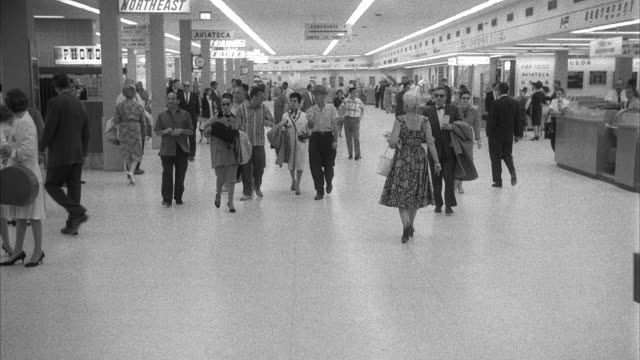vidéos et rushes de ms people walking in front of ticket counters at miami airport terminal - 1960
