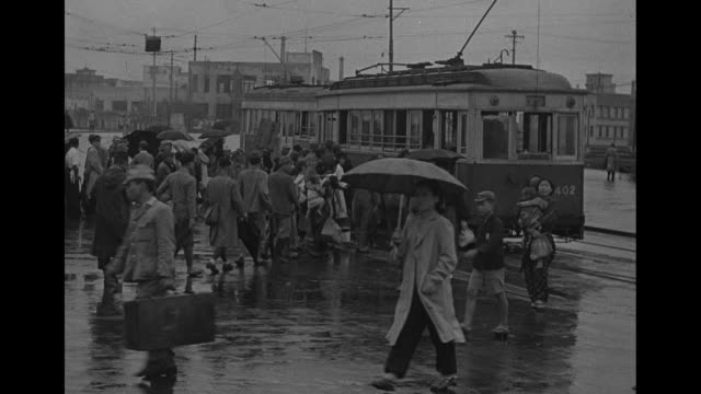 people walking in front of train station / train pulls into station / two shots of people getting on trolley / us soldier searches japanese civilian... - japanese military stock videos & royalty-free footage