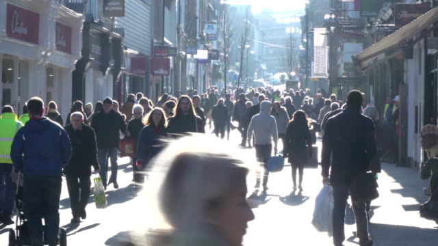 4K people walking in High Street backlit by sun