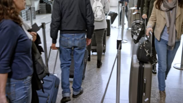 People walking in line towards the check in desk at the airport with their luggage