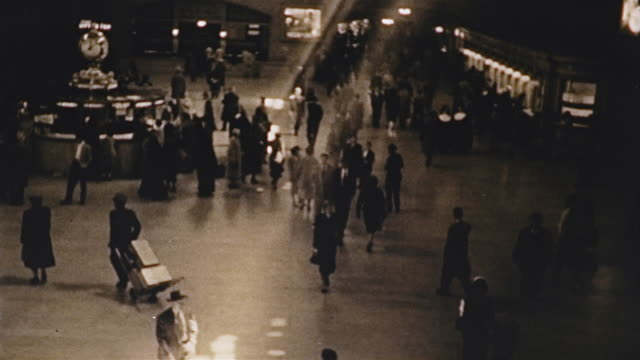 vidéos et rushes de 1953 ha ws people walking in main hall of grand central station with light streaming in / manhattan, new york - 1953