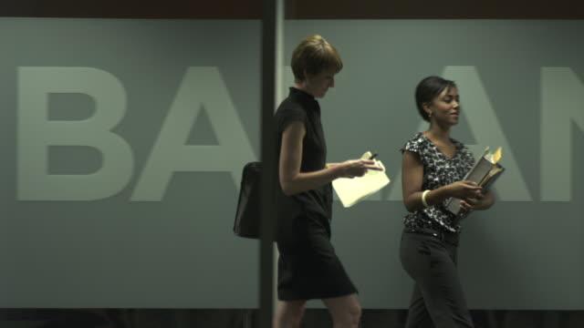 vídeos de stock, filmes e b-roll de ms pan people walking in office corridor, chicago, illinois, usa - escrita ocidental