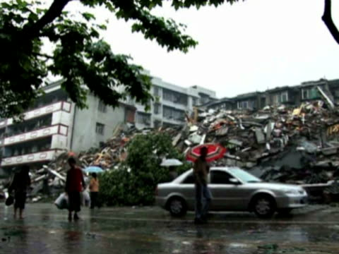 People walking in rain past ruined buildings after earthquake on May 12 2008 in Beichuan County about 160 km or 99 miles northeast of quake epicenter...