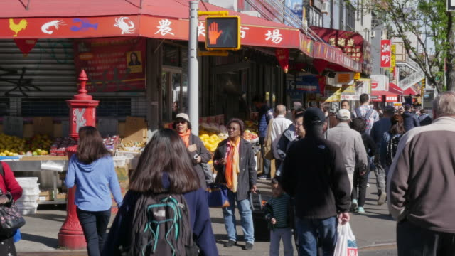 People walking in shopping street in Flushing, Queens, New York