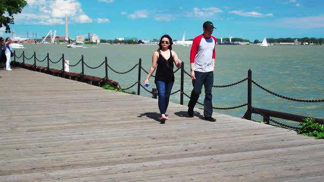stockvideo's en b-roll-footage met people walking in the boardwalk of the city's waterfront on june 24 in toronto, ontario, canada. lake ontario has an unusually high level of waters... - loop elementen