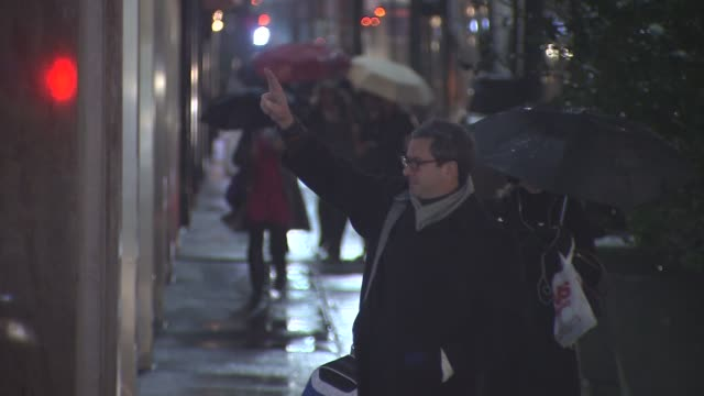 People Walking in the Rain at Night A Man Tries to Hail a Cab in the Rain on November 27 2013 in New York New York