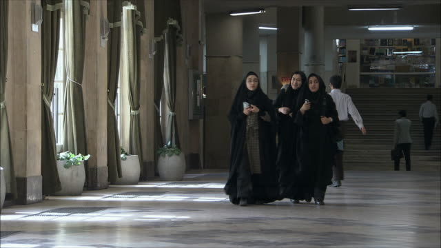 vídeos de stock, filmes e b-roll de ws people walking in university hall, tehran, iran - irã