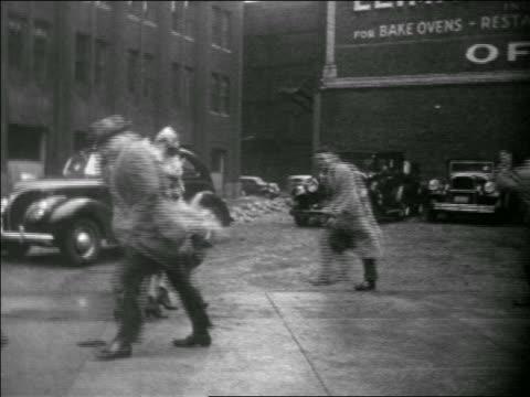 b/w 1939 people walking in violent windy rainstorm on city sidewalk / educational - 1930 1939 video stock e b–roll