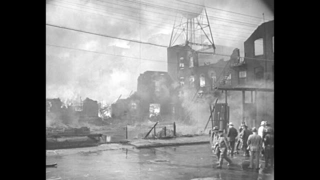 people walking near burning factory / firemen spraying fire with fire hose as other firemen stand next to them / people standing near burning factory... - fire hose stock videos & royalty-free footage