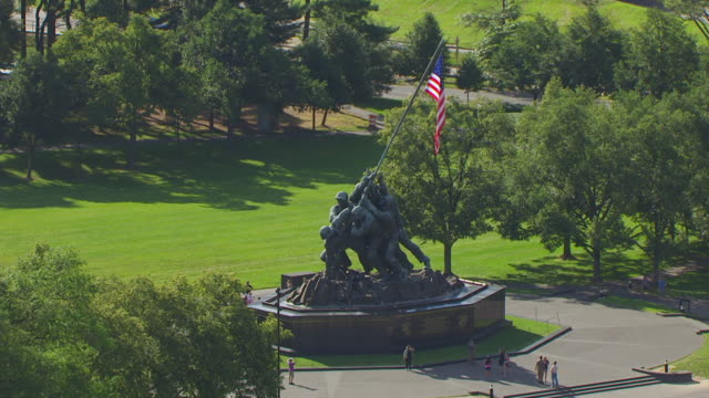 ws aerial pov people walking near marine corps war memorial, vehicles moving on street in background / arlington county, virginia, united states  - arlington virginia video stock e b–roll