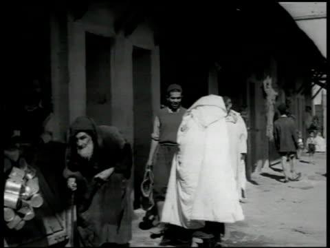 vidéos et rushes de people walking next to building. elder jewish male cobbler holding footbed, tinsmith, tinner working. jewish cobbler finishing sole of shoe. - judaism