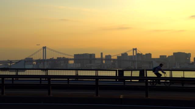 vídeos de stock, filmes e b-roll de pessoas andando em uma ponte. baía de tóquio e ponte arco-íris ao anoitecer / ciclista andando - porto distrito