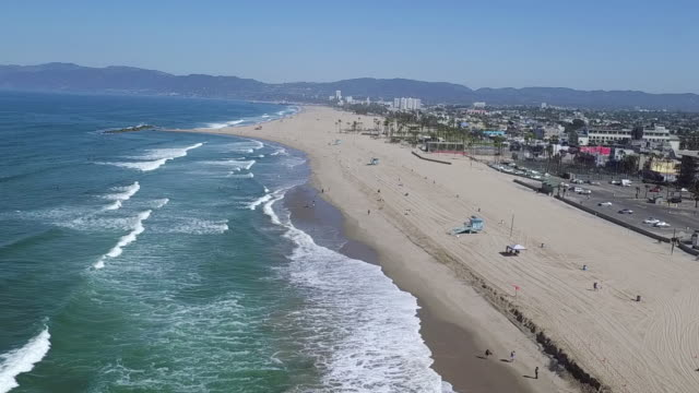 WS AERIAL POV People walking on beach / Venice, City of Los Angeles, California, United States