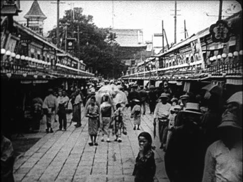 B/W 1923 people walking on boardwalk on Tokyo street / Japan / newsreel