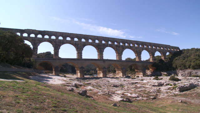 ms people walking on bridge / vers-pont-du-gard, provence ,france - riverbed stock videos & royalty-free footage