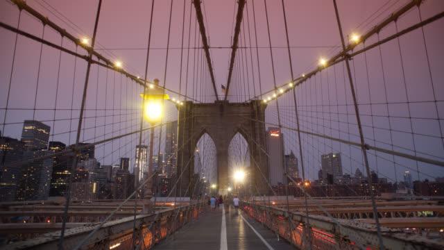 ws t/l people walking on brooklyn bridge, modern skyline in background / new york city, new york state, united states - brooklyn bridge stock videos & royalty-free footage