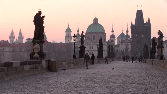 stockvideo's en b-roll-footage met ms people walking on charles bridge at morning and pink glow sky background  / prague, hlavni mesto praha, czech republic - praag