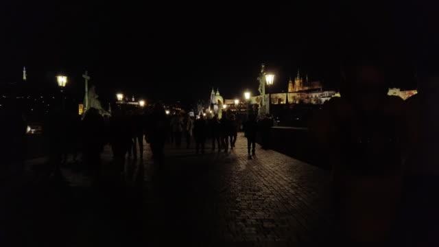 people walking on charles bridge in prague at night - hradcany castle stock videos & royalty-free footage