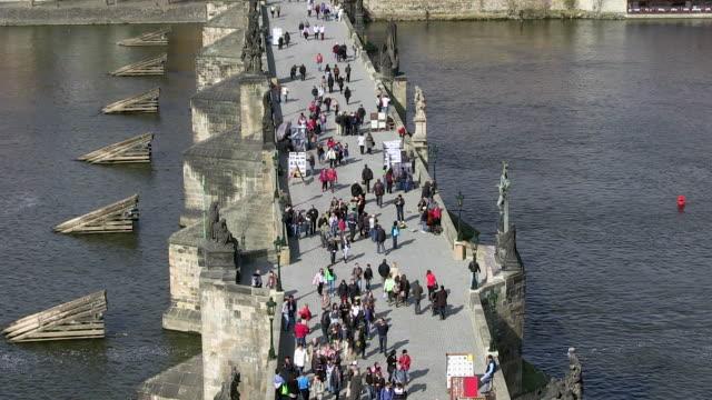 ms people walking on charles bridge over vltava river / prague, hlavni mesto praha, czech republic - charles bridge stock videos & royalty-free footage