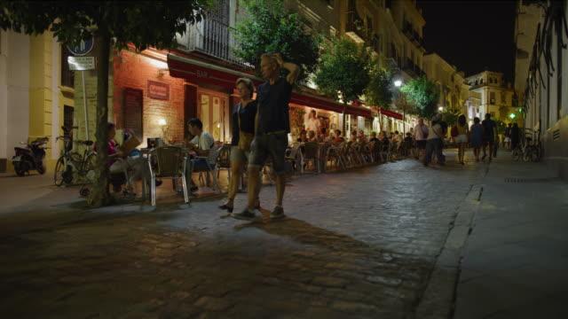people walking on cobblestone street at night near sidewalk cafe / seville, seville, spain - cobblestone stock videos & royalty-free footage