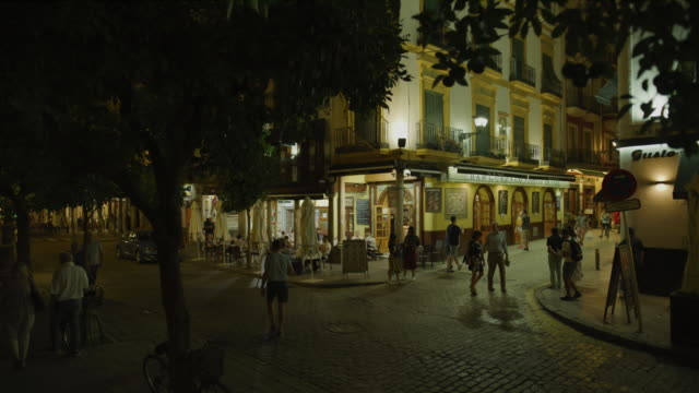 people walking on cobblestone street at night near sidewalk cafe / seville, seville, spain - spain stock videos & royalty-free footage