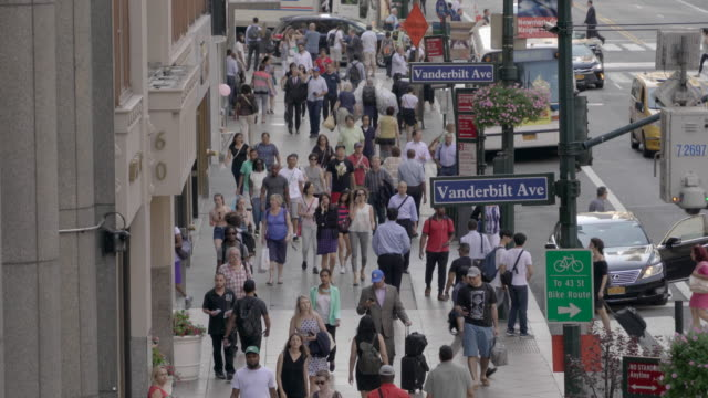 people walking on crowded city street. manhattan rush hour commuters scene. urban metropolis lifestyle