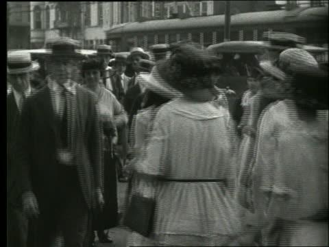 b/w people walking on crowded sidewalk / new orleans / 1915 / no sound - 1915年点の映像素材/bロール