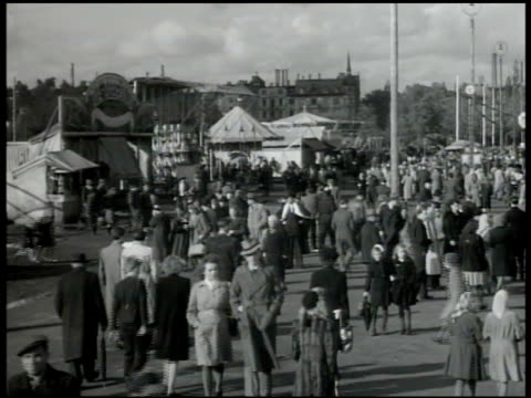 people walking on fairgrounds w/ booths rides amusement bg us soldier walking w/ woman in park - 1947 stock-videos und b-roll-filmmaterial