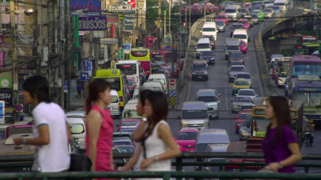 ms selective focus people walking on footbridge over gridlocked downtown road, bangkok, ayuthaya, thailand - see other clips from this shoot 1448 stock videos and b-roll footage