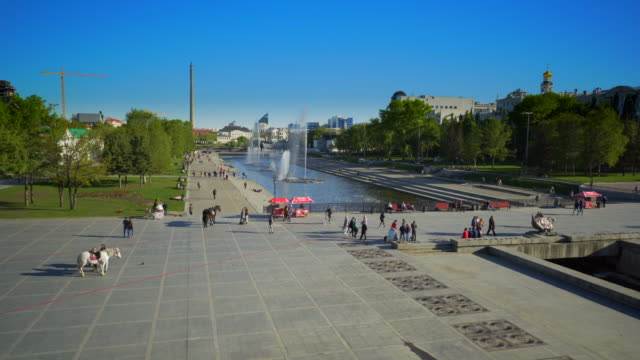 people walking on footpath by fountain at park during sunny day - yekaterinburg, russia - large group of animals点の映像素材/bロール
