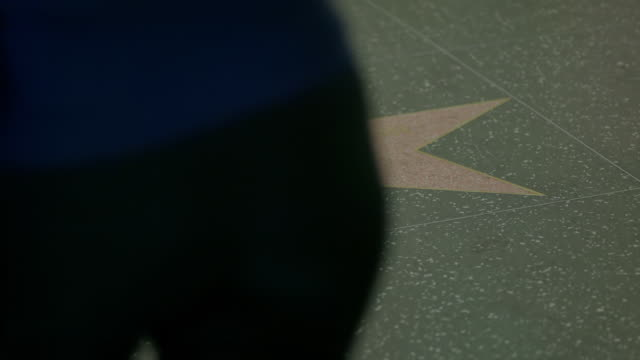 ms pan people walking on hollywood walk of fame, low section / hollywood boulevard, hollywood, city of los angeles, california, united states - ウォークオブフェーム点の映像素材/bロール